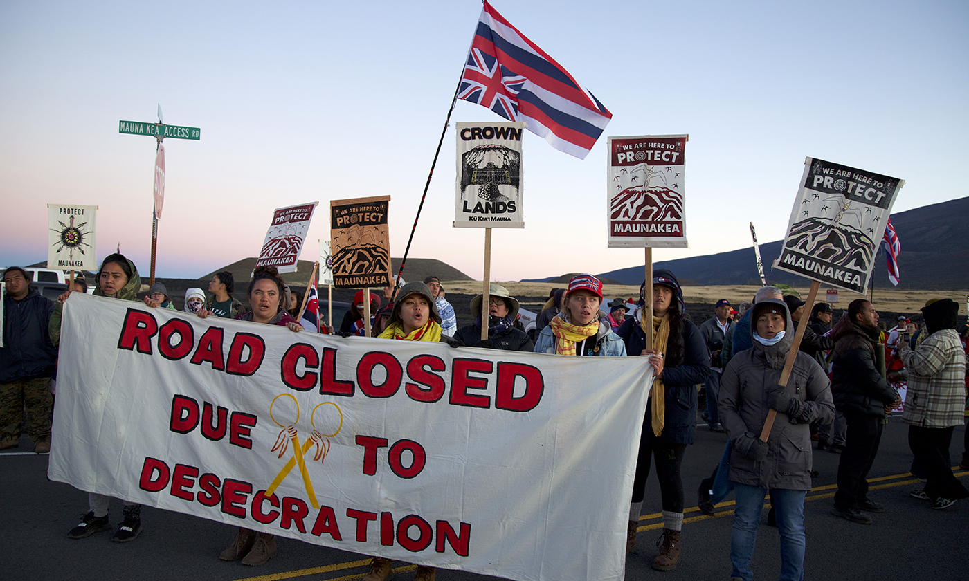 "image of Mauna Kea protest, with large sign in foreground reading ""Road closed due to desecration"