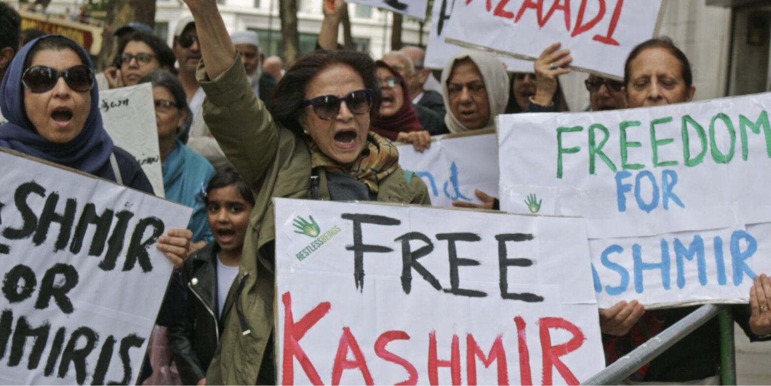 "photo of mostly women protesting, arms up in fists, holding signs such as ""Free Kashmir"" and ""Freedom for Kashmir"""