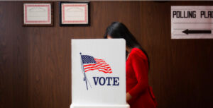 photo of woman, partially obscured, leaning into a voting booth