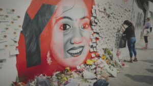 film still of woman signing a card on what appears to be a memorial mural from the film The 8th