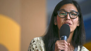 portrait of Ai-jen Poo speaking into a microphone she is holding