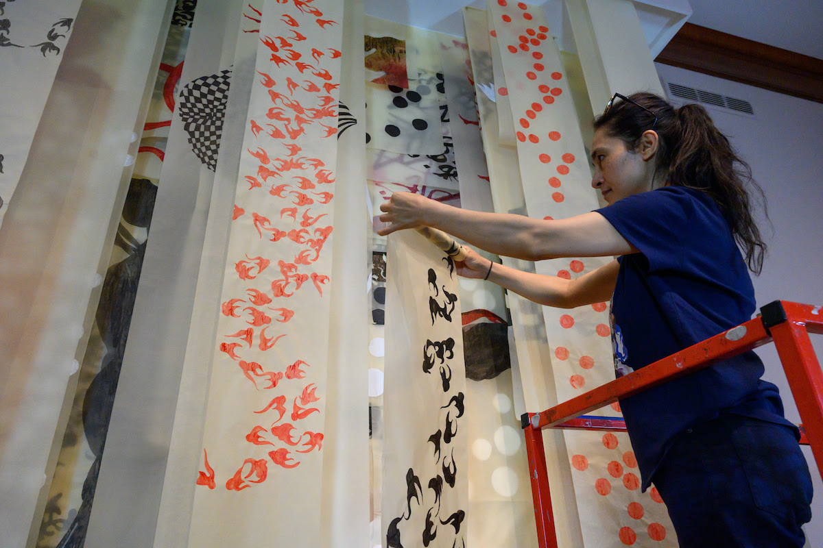 image of Shahzia Sikander on a ladder installing her show at the Morgan Library Museum