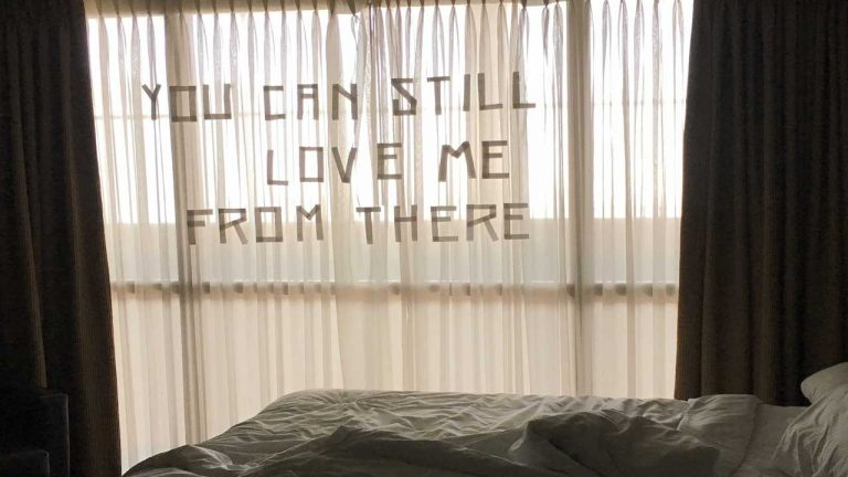 a hotel window during the day, drapes open, in front of an unmade bed, with the following text on the sheer curtains: You Can Still Love Me From There