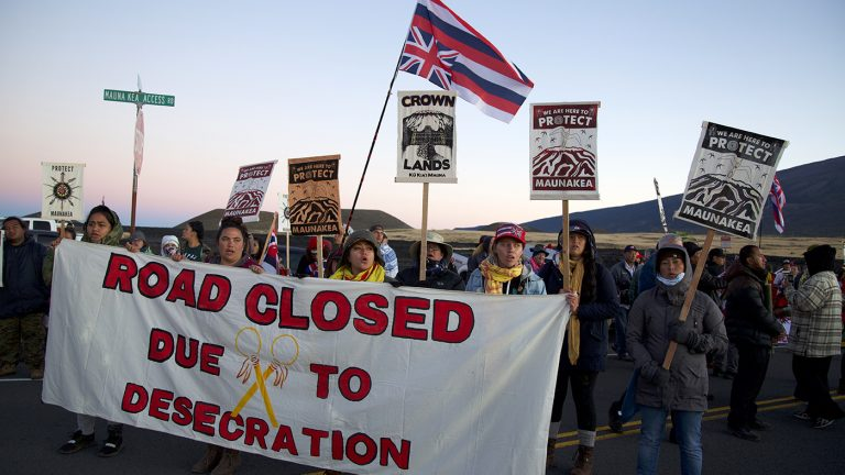 image of Mauna Kea protest, with large sign in foreground reading